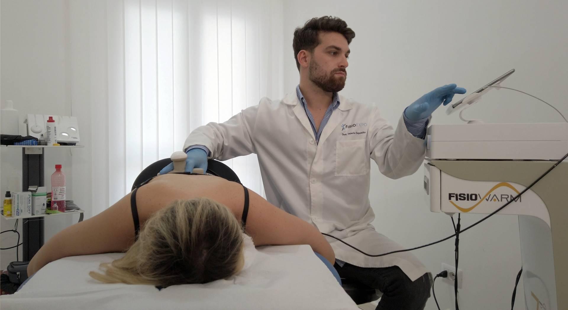 Il fisioterapista utilizza il macchinario per una tecarterapia alla schiena